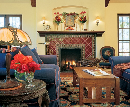 caption: The seating area of the living room. Ronstadt salvaged the needlepoint chair next to the fireplace from a sidewalk in San Francisco and wheeled it back to her house. The lamp, which was purchased in London, rests atop an elephant-motif table from India.